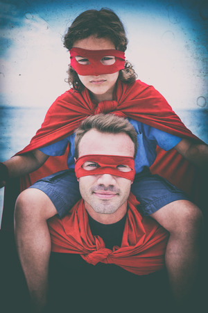shoulder carrying: Portrait of confident father in superhero costume carrying son on shoulder at beach