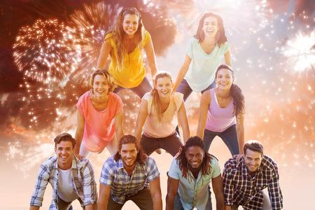 piramide humana: Amigos felices que hacen pirámide humana contra la explosión de fuegos artificiales de colores sobre fondo negro