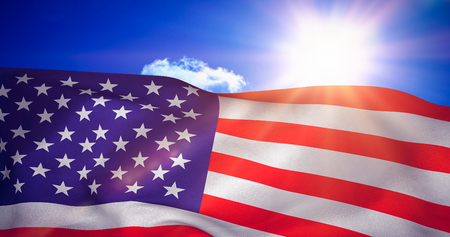 red america: American flag against bright blue sky with clouds