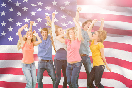 partying: Friends partying together while laughing and smiling against close-up of american flag