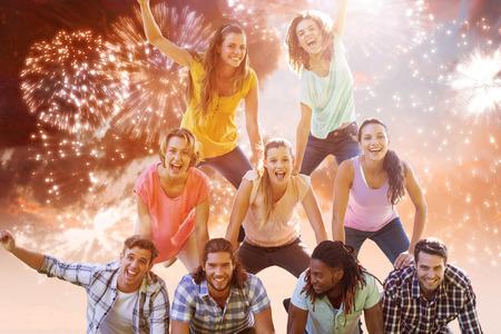 human pyramid: Amigos felices en el parque que hace la pirámide humana contra la explosión de fuegos artificiales de colores sobre fondo negro Foto de archivo