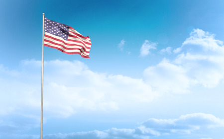 American flag waving on pole against cloudy sky background Stock Photo