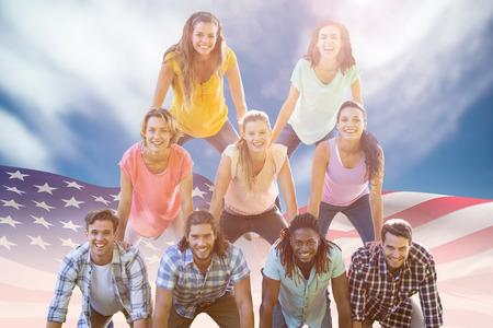 human pyramid: Amigos felices que hacen pirámide humana contra la vista de un cielo azul