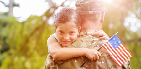 Portrait des lächelnden Mädchens amerikanische Flagge hält, während Armeeoffizier Vater im Park umarmt Lizenzfreie Bilder - 58741812