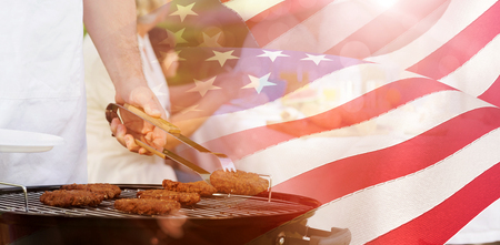 extended family: Barbecue grill with extended family having lunch in park against waving flag of america Stock Photo