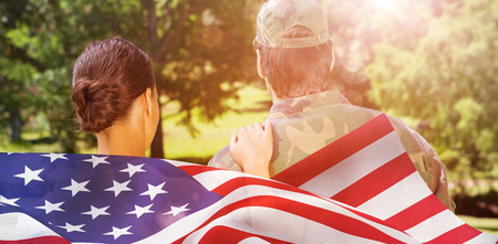 mid adult men: Rear view of solider and wife against focus on usa flag Stock Photo