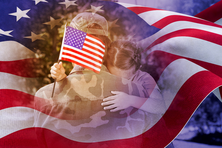 mid adult men: Army man hugging daughter with American flag against focus on usa flag