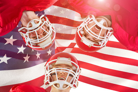American football huddle against focus on usa flag