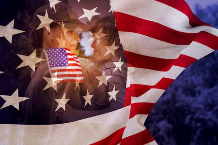 one parent: Army woman carrying son against focus on usa flag Stock Photo