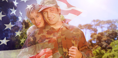 mid adult men: Portrait of simling army man with wife against focus on usa flag