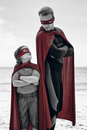 one parent: Father and son in superhero costume standing with arms crossed at beach
