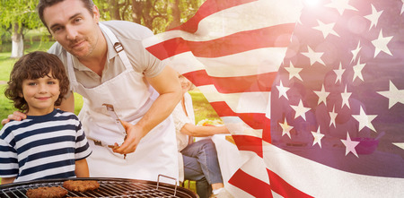mid adult men: Father and son at barbecue grill with family having lunch in park against focus on usa flag