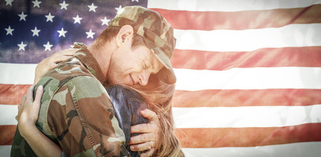 mid distance: American soldier embracing his partner in front of american flag while reuniting