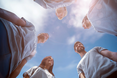 low angle view: Low angle view of friends together against view of a blue sky