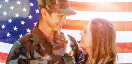 mid distance: Happy american soldier reunited with his partner in front of american flag