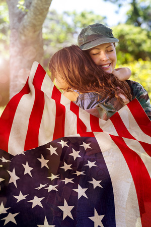 closeness: Focus on usa FLAG against happy soldier reunited with her daughter Stock Photo