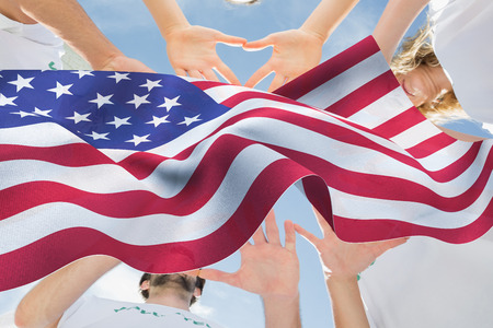 altruism: Volunteers with hands together against blue sky against focus on usa flag