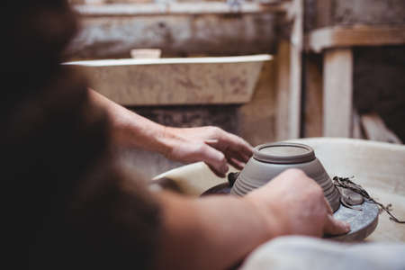 ceramicist: Cropped image of craftsperson making ceramic container in workshop