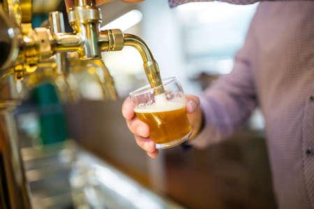 beer pump: Brewer filling beer in beer glass from beer pump in bar