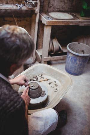 ceramicist: Craftsman preparing ceramic container in workshop