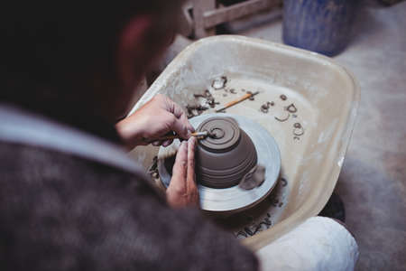 ceramicist: Rear view of craftsman making ceramic container in workshop LANG_EVOIMAGES