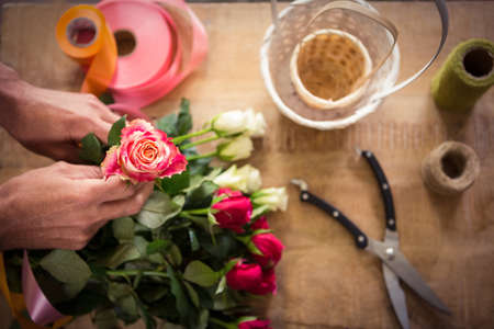 wicker work: Close-up of male florist preparing bouquet of flower at his flower shop