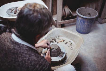ceramicist: Rear view of craftsman preparing ceramic container in workshop LANG_EVOIMAGES