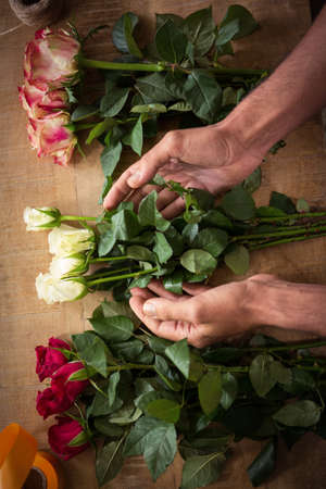 worktop: Male florist arranging flowers on the wooden worktop at his flower shop