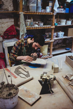 causal clothing: High angle view of focused young man working at workshop LANG_EVOIMAGES