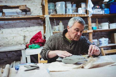 causal clothing: Focused mature man working at workshop LANG_EVOIMAGES