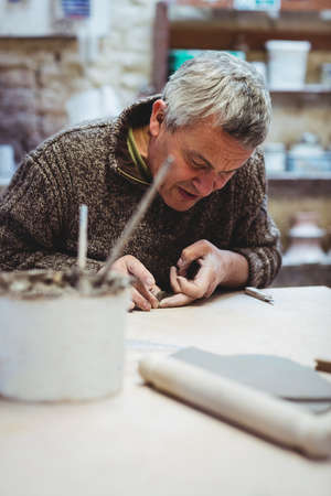 craftsperson: Concentrated craftsperson working at table in workshop LANG_EVOIMAGES