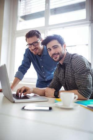 editors: Portrait of photo editors using laptop in creative office