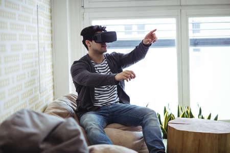 virtual reality simulator: Photo editor gesturing while using virtual reality simulator in creative office LANG_EVOIMAGES