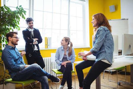 legs crossed on knee: Business people talking in creative office