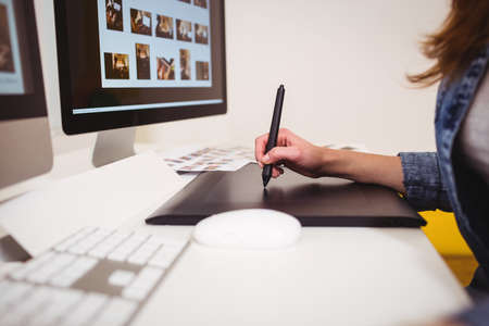 graphics tablet: Midsection of photo editor using graphics tablet at creative office LANG_EVOIMAGES