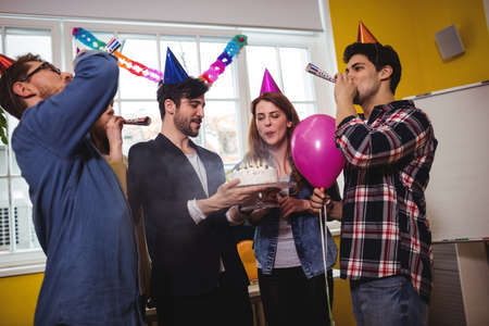 blowers: Business people celebrating birthday with horn blowers in creative office LANG_EVOIMAGES