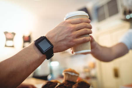 taking refreshment: Close-up of customer with smart watch taking fresh coffee from male barista at cafe LANG_EVOIMAGES