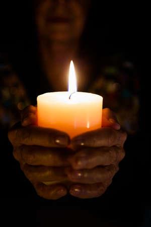 darkroom: Cropped image of female fortune teller holding lit candle in darkroom