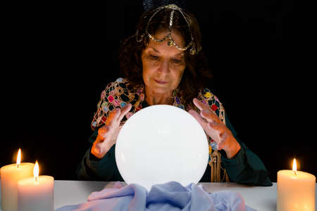 darkroom: Mature fortune teller with crystal ball while forecasting in darkroom