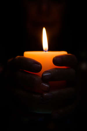 lit image: Cropped image of fortune teller holding lit candle in darkroom