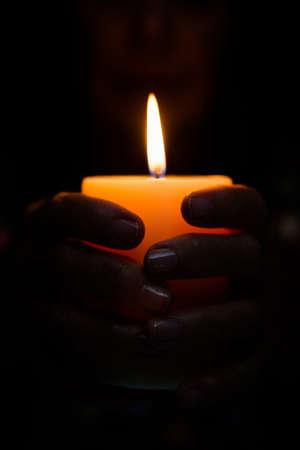 darkroom: Cropped image of fortune teller holding lit candle in darkroom