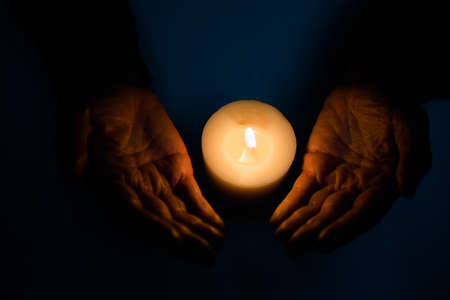 darkroom: Midsection of fortune teller with lit candle in darkroom LANG_EVOIMAGES