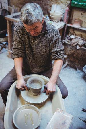 causal clothing: Focused mature man making pot at workshop