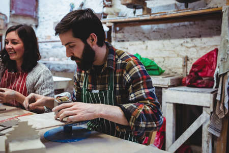 causal clothing: Smiling woman with male colleague working at workshop LANG_EVOIMAGES