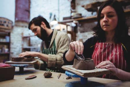 alfarero: alfarero de sexo femenino concentrado con su colega en la mesa de trabajo en el taller