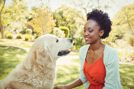 stroking: Woman posing with her dog at park