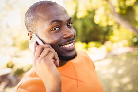 phoning: Happy man calling on the phone at park