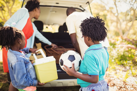 fond of children: Family removing stuff in the car Stock Photo
