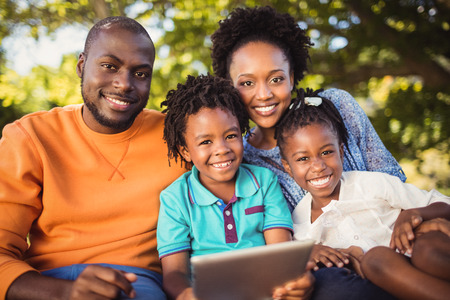 woman tablet pc: Happy family posing together at park