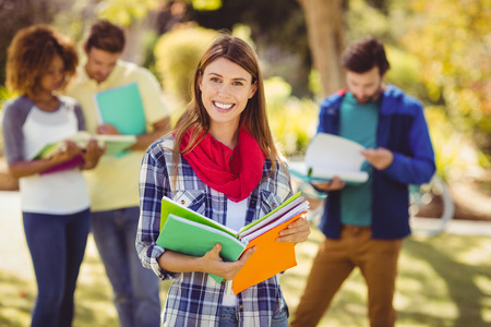 holding notes: Portrait of college girl holding notes with friends in background at campus